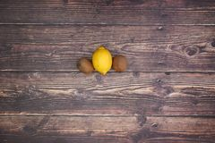 Lemon and 2 kiwis on wooden table.  stock photography