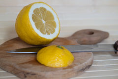 Lemon and knife. On a chopping board Stock Image