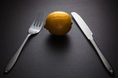 Lemon with knife and fork on black Stock Photography