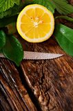 Lemon and knife. On wooden board. Stock Photography