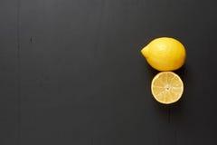 Lemon and lemon slice. Clearance black background. Lemon and lemon slice black wooden background Royalty Free Stock Images