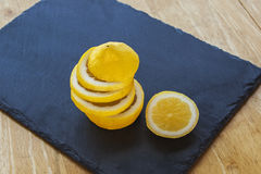 Lemon and lemon slices, juicy and ripe, on slate. Stock Images
