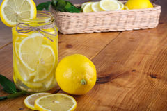 Lemon. Ade with some fresh uncut yellow  in wooden kitchen table Royalty Free Stock Images