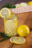 Lemon. Ade with some fresh uncut yellow  in wooden kitchen table Royalty Free Stock Image