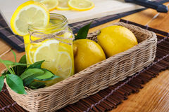 Lemon. Ade with some fresh uncut yellow  in wooden kitchen table Stock Photos