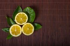Lemon. Lemons. Fresh ripe lemons on a dark background of bamboo. Top view Stock Photos