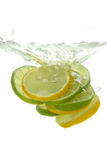 Lemon and lime. Thrown into the water with splash, on white background stock photos