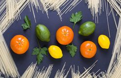 Lemon and lime on a black background. Lemon lime and tangerines on a black background. Citrus fruits with pasta on a black background Royalty Free Stock Image