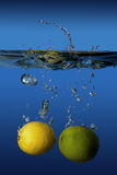 Lemon and lime dropped into water Royalty Free Stock Photos