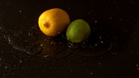 Lemon and lime dropping on wet black surface stock footage