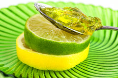 Lemon and lime fruit slices with marmalade. Closeup of lemon and lime fruit slices on a green swirl glass plate with a spoon of marmalade on top Royalty Free Stock Photos