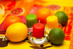 Lemon, lime and mandarin on table with candles. Royalty Free Stock Photo