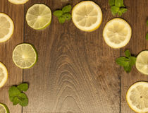 Lemon, lime and mint background. On wooden background Royalty Free Stock Photography