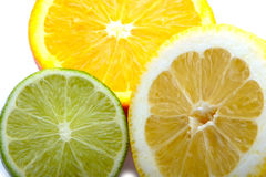 A Lemon, Lime and an orange cut. In half citrus on a white background close up royalty free stock photo