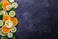 Lemon, lime and orange. Slices of ripe citruses. Lemon, lime and orange on dark stone background. Top view with copy space royalty free stock image