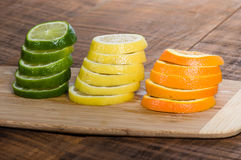 Lemon, lime and orange slices. Stacks of lemon, lime and orange slices on cutting board stock photo