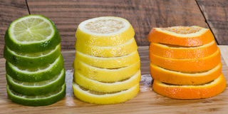 Lemon, lime and orange slices. Stacks of lemon, lime and orange slices on cutting board stock image