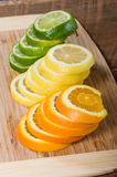 Lemon, lime and orange slices. Stacks of lemon, lime and orange slices on cutting board royalty free stock photography