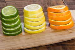 Lemon, lime and orange slices. Stacks of lemon, lime and orange slices on cutting board royalty free stock image