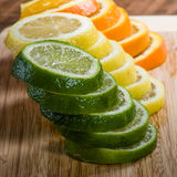 Lemon, lime and orange slices. Stacks of lemon, lime and orange slices on cutting board stock photography