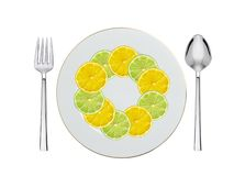 Lemon and lime slices plate, spoon and fork isolated on white Stock Photos