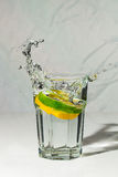 Lemon and lime water splash in glass Stock Photos