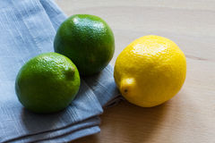 Lemon and limes with grey cloth on wooden background Royalty Free Stock Photography