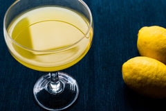 Lemon Liqueur Limoncello with lemon on dark blue surface. Lemon Liqueur Limoncello with lemon on white wooden surface. Beverage Concept Stock Image