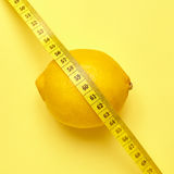 Lemon with measuring tape on a yellow background Royalty Free Stock Image
