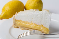 Lemon meringe pie slice with fork and lemons Stock Photos