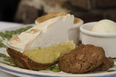 Lemon meringue pie and cookie on plate royalty free stock photography