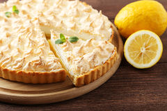 Lemon meringue pie. On cutting board on brown wooden background royalty free stock photos