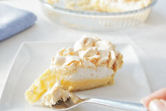 Lemon meringue pie. A slice of lemon meringue pie on a plate, with the pie dish in the background, and a piece of pie on a fork ready to be eaten Stock Photo