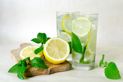 Lemon mint detox water. Home-made lemonade with mint, lemon and ice in glasses. Wooden board, sliced lemon and mint leaves Stock Photos
