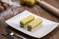 Lemon and mint pastry on a plate with eggs lemons and fork knife on a wooden table Stock Images