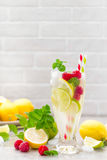Lemon mojito cocktail with lime, mint and raspberry, cold drink with ice. Stock photo Stock Photo