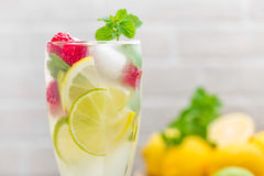 Lemon mojito cocktail with lime, mint and raspberry, cold drink with ice. Stock photo Royalty Free Stock Images
