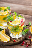 Lemon mojito cocktail with mint and pomegranate Stock Photos