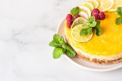Free Lemon Mousse Vanilla Cheesecake With Lemon Curd Decorated By Lemon And Lime Slices, Frozen Raspberry And Mint. Stock Image - 169286111