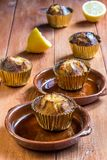 Lemon muffins. In golden cases on wooden table board stock photography