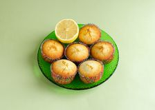 Lemon muffins set on plate. Lemon muffins with piece of lemon on green glass plate on pale green background Stock Photos