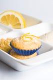 Lemon muffins in white tray. Two freshlu baked lemon muffins in blue collars on white tray with slice of lemon Royalty Free Stock Image