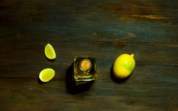 Lemon oil in a glass bottle on a wooden background, close up royalty free stock photo