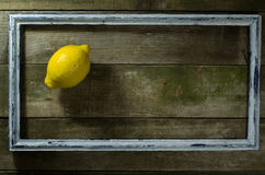 Lemon in the old frame. On a wooden background royalty free stock photography