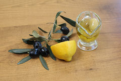 Lemon and olive oil with olives. On the wooden table Stock Photography