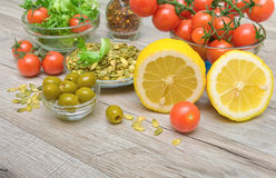 Lemon, olives and other food on a wooden table Stock Images