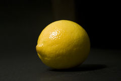 Lemon, one lightspot, black background. Yellow lemon on black background Royalty Free Stock Image