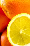 Lemon and Orange. A yellow lemon in the front. Oranges out of focus in the background Stock Image