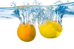 Lemon and orange  fell into the water. Close-up Royalty Free Stock Image
