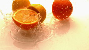 Lemon and orange halves falling and bouncing on white wet surface stock footage